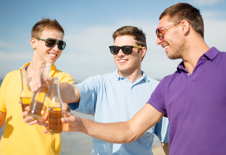 nonalcoholic beer: summer, holidays, vacation and happy people concept - group of friends having fun on the beach with bottles of beer or non-alcoholic drinks