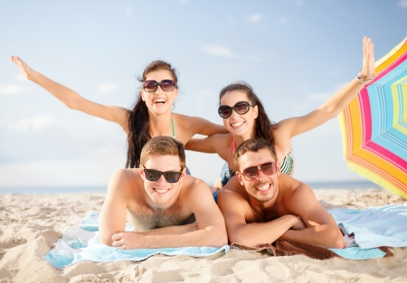 outstretched arms: summer, holidays, vacation and happy people concept - group of smiling people in sunglasses having fun on the beach Stock Photo