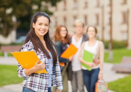 summer holidays, education, campus and teenage concept - smiling female student in with folders and group in the back Stock fotó