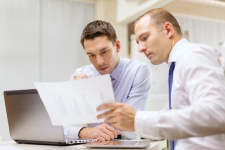 business, technology and office concept - two businessmen with laptop, tablet pc computer and papers having discussion in office photo