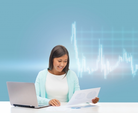 business, money and technology concept - asian businesswoman or student with laptop, forex chart and documents in office photo