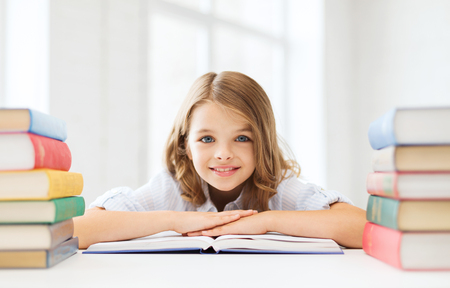 nice girl: education and school concept - smiling little student girl with many books at school Stock Photo