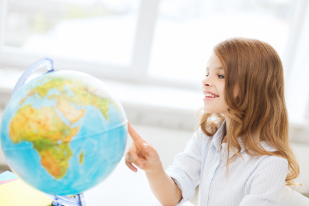 education and school concept - smilng little student girl with globe at school photo