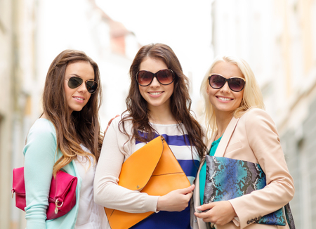 accesories: holidays, tourism and happy people concept - three smiling women in sunglasses with bags in the city