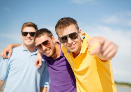 invitando: verano, vacaciones, vacaciones y concepto de la felicidad - grupo de amigos que se divierten en la playa y apuntando a usted Foto de archivo