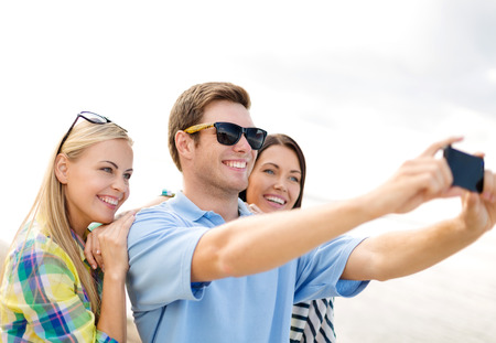 summer, holidays, vacation and happiness concept - group of friends taking picture with smartphone photo