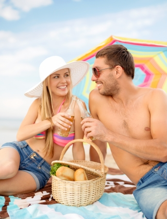 nonalcoholic beer: summer, holidays, vacation and happy people concept - smiling couple having picnic on the beach under colorful umbrella