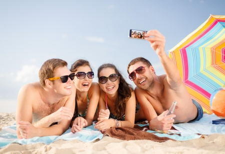 camera phone: summer, holidays, vacation, technology and happiness concept - group of smiling people in sunglasses taking picture with smartphone on beach