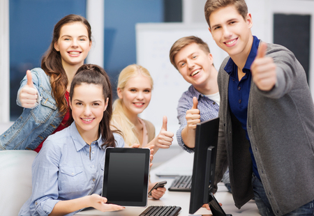 education, advertisement, techology and internet concept - group of smiling students with computer monitor and blank black tablet pc screen photo