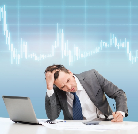 business, office and money concept - stressed businessman in black eyelgasses with laptop computer, papers, calculator and forex chart photo