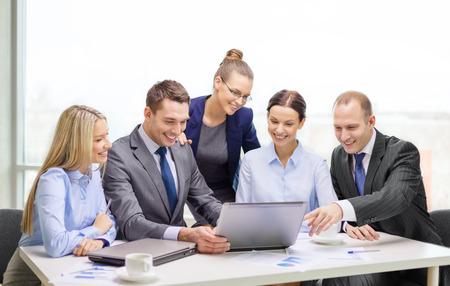business, technologie en kantoorconcept - lachend business team met laptop computers, documenten en koffie die discussie in het kantoor