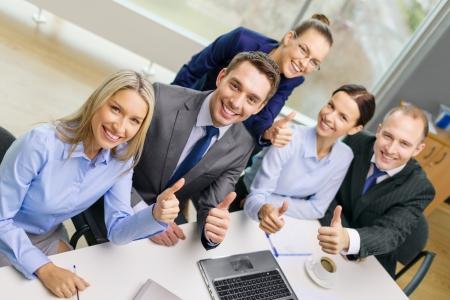 zakelijk, succes, technologie en kantoorconcept - lachend business team met laptop, papieren en koffie met thumbs up in kantoor