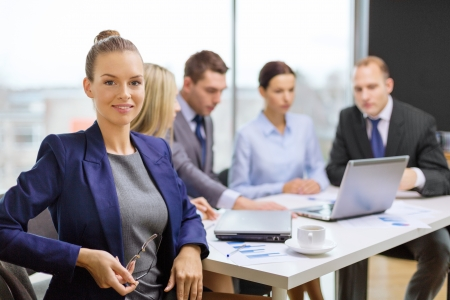 entrepreneurs: business, technology and office concept - smiling businesswoman with eyeglasses in office with team on the back