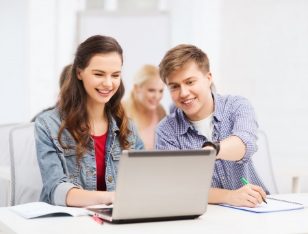 education technology: education, technology and internet concept - two smiling students with laptop and notebooks at school Stock Photo