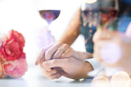 love, family, anniversary concept - engaged couple with wine glasses in restaurant photo