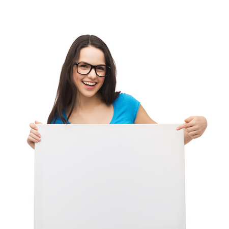 vision, health, advertisement and people concept - smiling girl wearing eyeglasses pointing finger to white blank board photo
