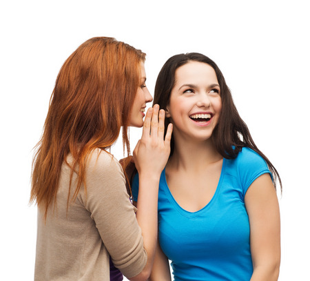 hearsay: friendship, happiness and people concept - two smiling girls whispering gossip