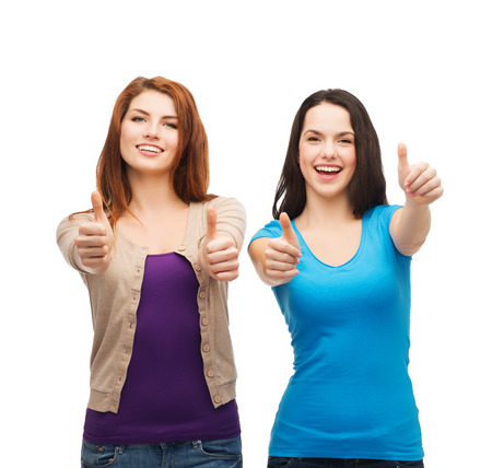 teenagers laughing: friendship and happy people concept - two smiling girls showing thumbs up Stock Photo