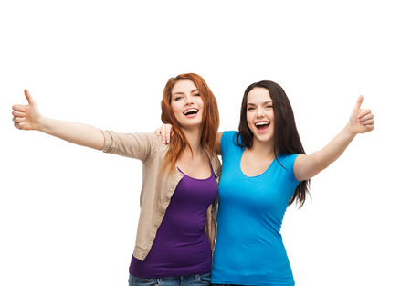 thumbs up gesture: friendship and happy people concept - two smiling girls showing thumbs up Stock Photo