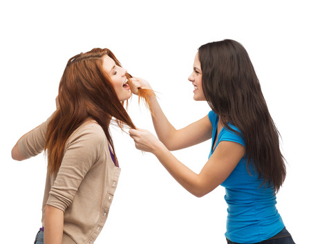 bullying, friendship and people concept - two teenagers having a fight and getting physical photo