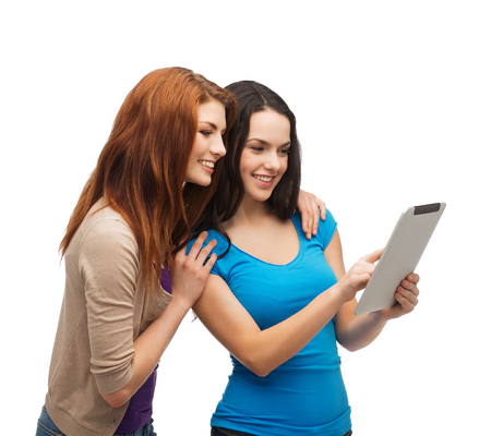 technology, friendship and people concept - two smiling teenagers pointing finger at tablet pc screen photo