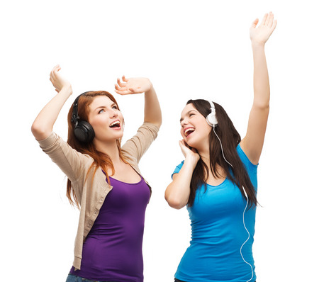 music and technology concept - two laughing teenagers with headphones dancing photo
