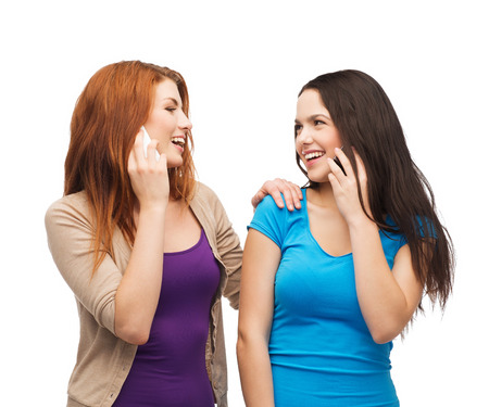 technology, friendship and leirure concept - two smiling teenagers talking with smartphones photo