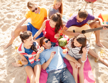 girl playing guitar: summer, holidays, vacation, music, happy people concept - group of friends with guitar having fun on the beach