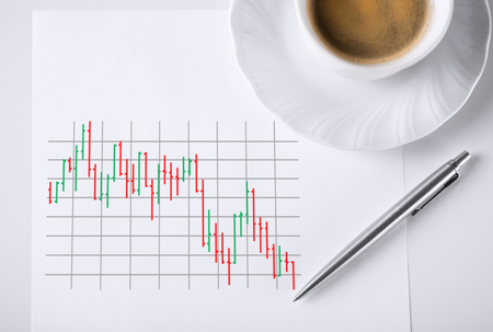 business and money concept - paper with forex chart in it and coffee photo