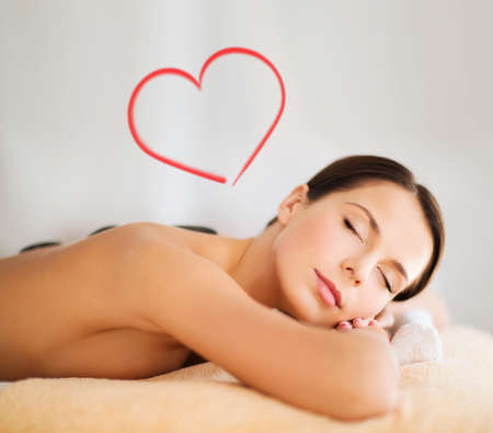 health and beauty, resort and relaxation concept - beautiful woman with closed eyes in spa salon with hot stones photo