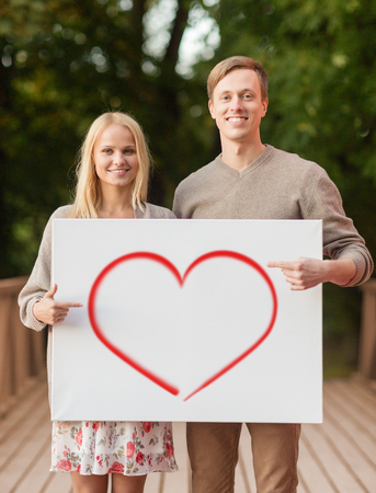 summer holidays, love, travel, relationship and advertisement concept - romantic couple on bridge pointing finger to white board with heart photo
