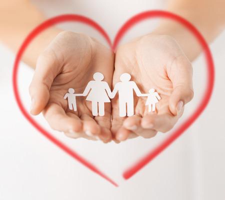 el amor, la familia y el concepto de la felicidad - Close up de manos de mujeres mostrando el hombre de papel de la familia