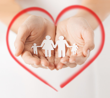 love, family and happiness concept - close up of womans hands showing paper man family photo