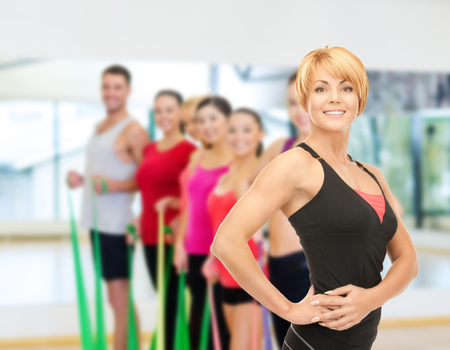 man working out: fitness, sport, training, gym and lifestyle concept - group of smiling people with trainer exercising in the gym