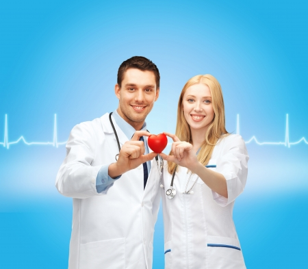 healthcare and medical concept - two young doctors cardiologists with heart photo