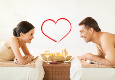 beauty wellness: kuuroord, schoonheid, liefde en geluk concept - lachende paar met kaarsen in spa salon drinken champagne Stockfoto