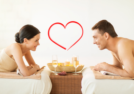 wellness center: spa, beauty, love and happiness concept - smiling couple with candles in spa salon drinking champagne