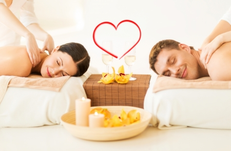 couples therapy: spa, beauty, love and happiness concept - smiling couple with candles, flowers and champagne glasses getting massage in spa salon Stock Photo