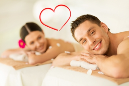 massage table: spa, beauty, love and happiness concept - smiling couple lying on massage table in spa salon Stock Photo