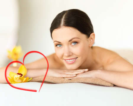 health and beauty, resort and relaxation concept - smiling woman in spa salon lying on the massage desk photo