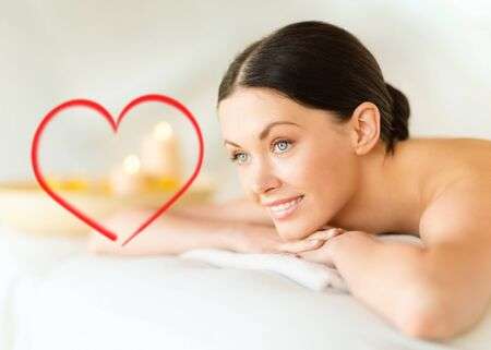 Massage: здоровье и красота, курорт и концепция релаксации - улыбается женщина в спа-салон, лежа на массажном столе