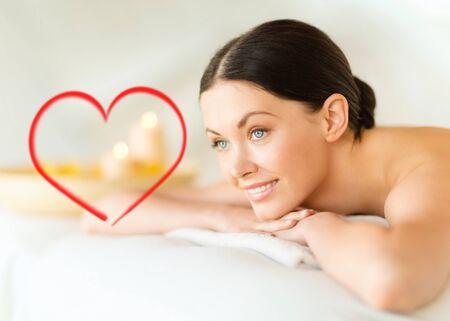 beauty wellness: gezondheid en schoonheid, complex en ontspanning concept - glimlachende vrouw in spa salon liggend op de massage bureau