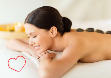 health and beauty, resort and relaxation concept - smiling woman in spa salon with hot stones photo
