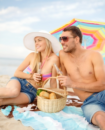 anniversary beach: summer, holidays, vacation and happy people concept - smiling couple having picnic on the beach under colorful umbrella