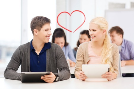 education technology: education, technology and internet - two smiling students looking at tablet pc in lecture at school