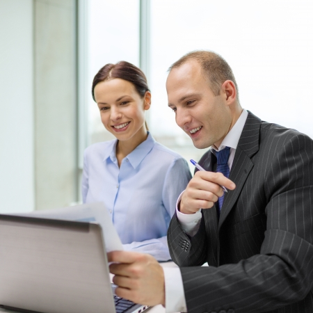 business, technology and office concept - businessman and businesswoman with laptop computer and papers having discussion in office photo