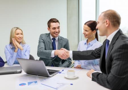 business, technologie en kantoorconcept - twee lachende zakenman handen schudden in het kantoor