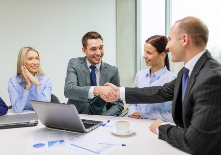 men shaking hands: business, technology and office concept - two smiling businessman shaking hands in office