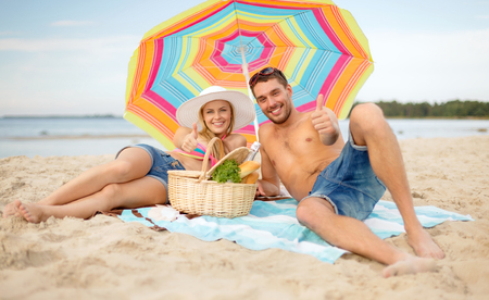 summer, holidays, vacation and happy people concept - smiling couple lying on the beach under colorful umbrella and showing thumbs up photo