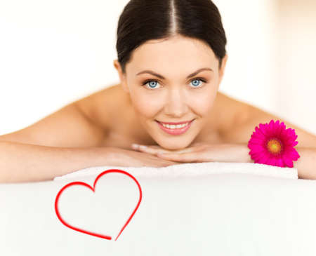spa, beauty, resort and relaxation concept - smiling woman with flower in spa salon lying on the massage desk Stock Photo - 24489190